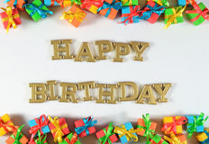 Goldener Text alles Gute zum Geburtstag und bunte Geschenke auf einem Weiß lizenzfreie stockfotos