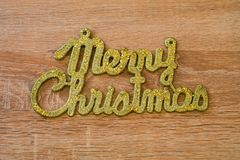 Goldener Text der frohen Weihnachten auf einem hölzernen Hintergrund lizenzfreie stockfotos