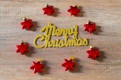 Goldener Text der frohen Weihnachten auf einem hölzernen Hintergrund umgeben durch rote Sternverzierungen lizenzfreie stockfotografie