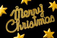 Goldener Text der frohen Weihnachten auf einem schwarzen Hintergrund mit Sternen stockfoto