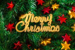 Goldener Text der frohen Weihnachten auf einem Weihnachtsbaumhintergrund mit den roten und gelben Sternen vektor abbildung