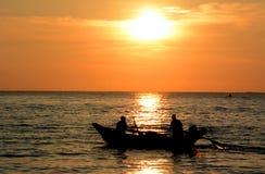Goldener tropischer Sonnenuntergang, Schattenbild von Fischern auf dem Horizont stockbild