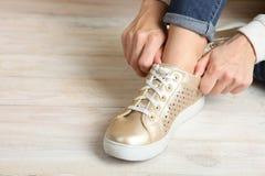Goldener Turnschuh am Mädchen auf dem Bein Lizenzfreie Stockbilder