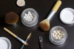 Goldener und Perlenleuchtmarker in Form von Bällen in einem offenen Glas Nah an der Bürste für das Anwenden von Kosmetik und von  Stockfotos