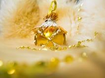 Goldener Weihnachtsball, der eine Mühlform hat, auf Schafpelzhintergrund mit Girlande Stockfotos