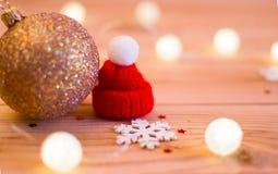Goldener Weihnachtsball mit einem roten Weihnachtshut lizenzfreie stockbilder