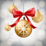 Goldener Weihnachtsball mit Schneeflocke und roter Bogen in den Schneefällen Lizenzfreies Stockfoto