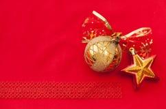 Goldener Weihnachtsball und -stern mit einem roten Bogen mit Schneeflocken Stockfoto