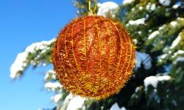 Goldener Weihnachtsflitter, der in einem Baum mit Schnee hängt Stockfotografie