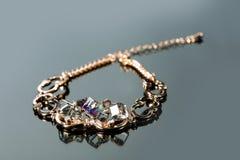 Goldenes Armband mit Edelsteinen auf Grau Stockfotos