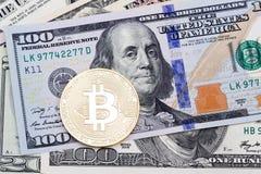 Goldenes bitcoin auf hundert Banknotenhintergrund Lizenzfreie Stockfotografie