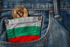 Goldenes BITCOIN ( BTC) cryptocurrency in der Tasche von Jeans mit Stockbilder