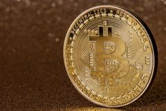 Goldenes bitcoin cryptocurrency auf glittery goldenem Hintergrund lizenzfreies stockbild