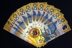 Goldenes Bitcoin, das auf Australier 50-Dollar-Banknoten auf schwarzem Hintergrund glüht Stockfotografie
