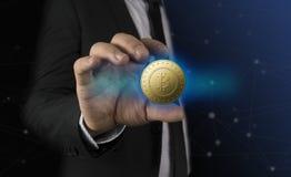 Goldenes bitcoin in der Hand des Geschäftsmannes mit schwarzem Anzug Lizenzfreie Stockfotos