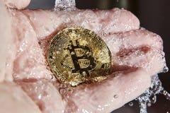 Goldenes bitcoin in der Palme einer Hand Euro, die oben nach Reinigung (Waschen, trocknen) stockbilder