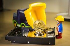 Goldenes Bitcoin tragen oder Laden auf einem LKW über einer Festplatte Lizenzfreies Stockfoto