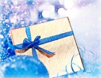 Goldenes blaues Weihnachtsgeschenk mit Flitter Stockfotografie