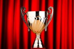 Goldenes Cup gegen roten Hintergrund Lizenzfreie Stockbilder
