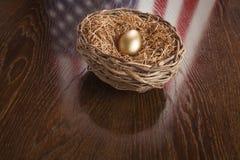 Goldenes Ei im Nest mit Reflexion der amerikanischen Flagge auf Tabelle Lizenzfreies Stockbild