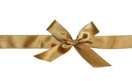 Goldenes Farbband und Bogen des Geschenks Stockfotografie
