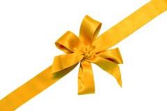 Goldenes Farbband und Bogen des Geschenks Stockfoto