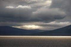Goldenes farbiges Sonnenlicht an der goldenen Stunde auf großem See mit drastischem und schwermütigem Landschaftshintergrund Stockfotos