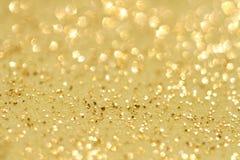 Goldenes Funkeln funkelt Staubhintergrund Stockbilder