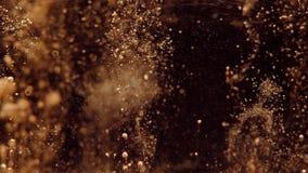 Goldenes Funkeln kommt in das Wasser mit einem schwarzen Hintergrund und vereinbart unten Umgedreht stock video footage