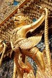 Goldenes Garuda steht auf dem Arm der Wand lizenzfreies stockbild