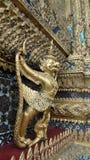 Goldenes Garuda und Nagas verzieren die Außenseite von Ubosoth von Wat Phra-kaew Stockfotografie