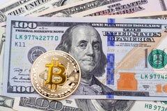 Goldenes gelbes bitcoin auf hundert Banknotenhintergrund Lizenzfreies Stockfoto