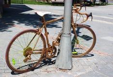 Goldenes gemaltes Fahrrad angekettet an einen Straßenlaternenpfahl Stockbilder