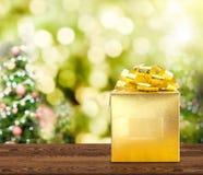 Goldenes Geschenk auf brauner hölzerner Tabelle mit Weihnachtsbaum verwischte b Lizenzfreie Stockfotos