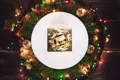 Goldenes Geschenk auf der Platte im Kranz Stockbilder