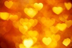 Goldenes Herz bokeh Hintergrundfoto, abstrakter Feiertagshintergrund Stockbilder
