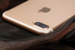 Goldenes iPhone 7 Plus auf abstraktem Hintergrund Stockbild