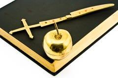 Goldenes Kreuz und Apple auf Bibel Stockfotografie