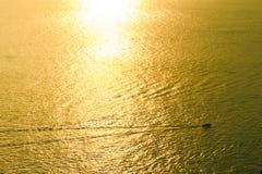 Goldenes Meer mit beweglichem Boot Stockfotos