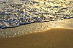 Goldenes Meerwasser, das auf dem Strand chashing ist Stockfotografie