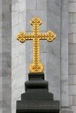 Goldenes orthodoxes Kreuz auf grauem Steinhintergrund Lizenzfreie Stockfotos