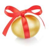 Goldenes Osterei mit rotem Bogen. Lizenzfreies Stockbild