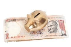 Goldenes Sparschwein auf Inder 1000 Rupie Lizenzfreies Stockfoto