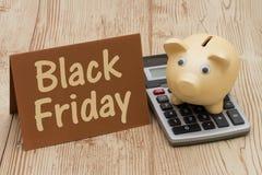 Goldenes Sparschwein Black Fridays, A, Karte und Taschenrechner auf Holz b Stockfotografie