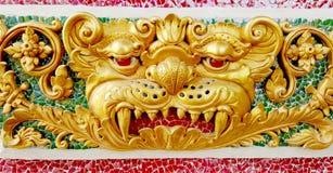 Goldenes verärgertes Gesicht der riesigen Statue auf keramischer Wand am Tempel Stockfoto