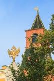 Goldenes Wappen der Russischen Föderation gegen den Hintergrund des mittleren Arsenal-Turms von Lizenzfreie Stockfotografie
