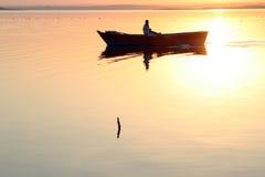 Goldenes Wasser des Bootsschattenbildes Stockfotografie