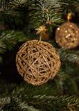 Goldenes Weihnachten flocht Kugel auf Weihnachtsbaumhintergrund. Stockfotos