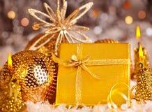 Goldenes Weihnachtsgeschenk mit Flitter und Kerzen Stockfoto