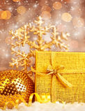 Goldenes Weihnachtsgeschenk mit Flitterdekorationen Lizenzfreie Stockbilder